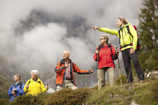 Young Female Hiking Guide Showing Senior Group Surrounding Mount