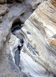 Hikers Walk Through The Narrows Of Mosaic Canyon